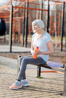 Breve pausa. allegra donna bionda in possesso di una bottiglia di succo di frutta e rilassarsi durante l'allenamento