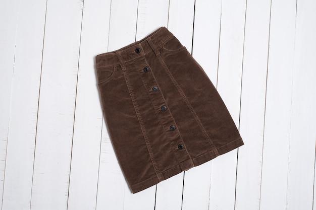 Gonna corta in velluto a coste marrone su fondo di legno bianco. concetto di moda.
