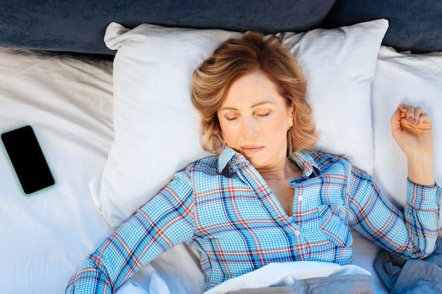 Donna adulta dai capelli corti. donna matura dai capelli chiari in pigiama a scacchi che allarga le mani mentre dorme sulla schiena