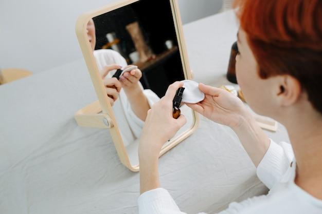 Donna dai capelli corti seduta davanti allo specchio, che applica acqua micellare. utilizzo di prodotti e cose eco-compatibili.