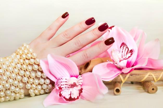 Breve manicure con orchidea e un braccialetto di perle sulla mano femminile si chiuda.