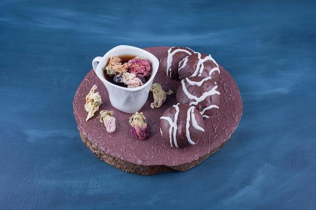 Biscotti di pasta frolla ricoperti di cioccolato bianco e fondente con una tazza di tè in vetro.