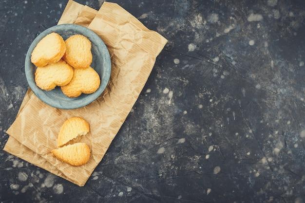 Biscotti di pasta frolla sotto forma di cuori in un piccolo piatto sul nero. vista dall'alto. copia spazio.