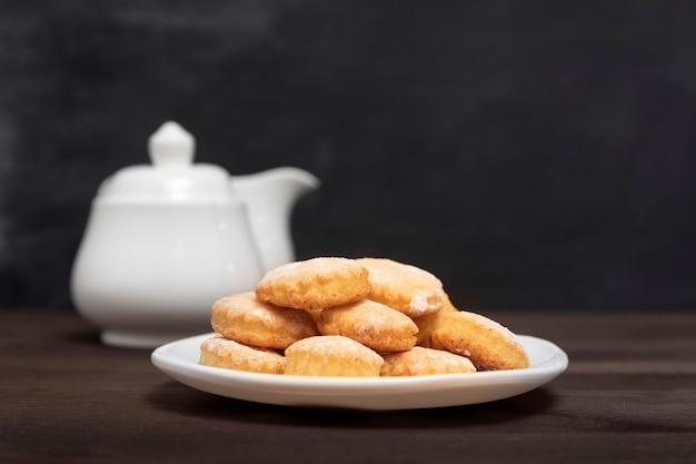 Biscotti di pasta frolla sul piatto bianco sulla tavola di legno, vista laterale. cuocere per il tè, pasticceria fresca