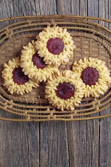 Biscotti di pasta frolla con marmellata su tavola in legno rustico
