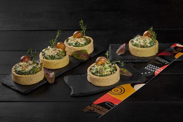 Crostate di pasta frolla con ripieno di crema di spinaci e lumache Foto Premium
