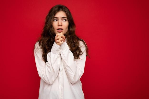 Colpo di attraente giovane donna bruna riccia interessata che indossa una camicia bianca isolata su red