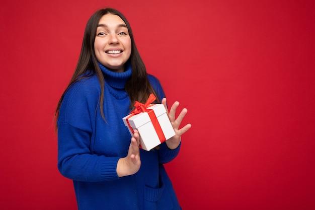 Colpo di attraente giovane donna bruna sorridente felice isolata su una parete di fondo rossa che indossa un maglione casual blu che tiene in mano una scatola regalo bianca e guarda la fotocamera
