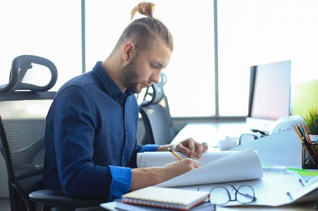 Inquadratura di un attraente architetto maschio che tiene in mano i piani mentre è seduto nel suo ufficio.