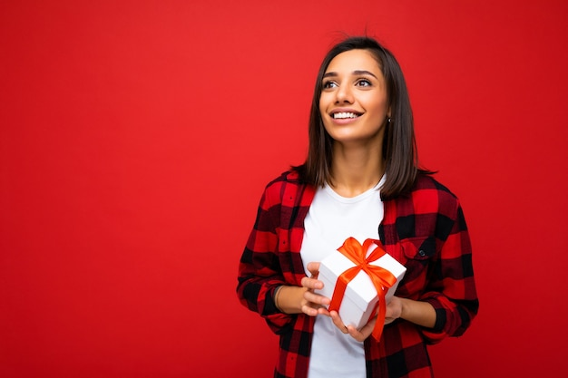 Colpo di attraente giovane donna bruna sorridente positiva isolata su sfondo colorato