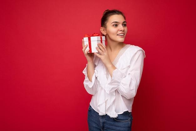 Colpo di attraente positiva sorridente giovane donna bruna isolata su sfondo rosso muro indossando camicetta bianca che tiene confezione regalo bianca con nastro rosso e guardando al lato.
