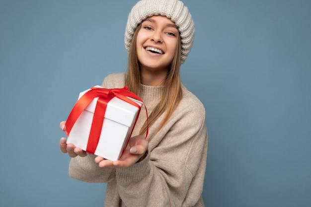 Colpo di attraente positiva sorridente giovane donna bionda scura isolata su sfondo colorato muro che indossa abiti alla moda tutti i giorni