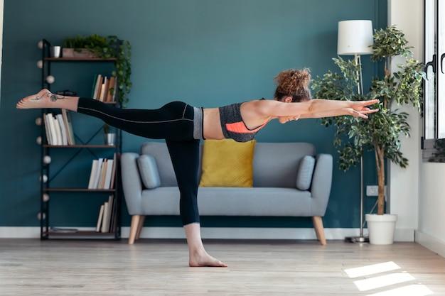 Colpo di attraente giovane donna sportiva che fa esercizi ipopressivi nel soggiorno di casa.