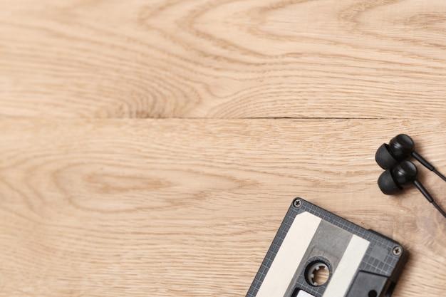 Colpo di audiocassetta e auricolari nell'angolo destro sulla superficie in legno.