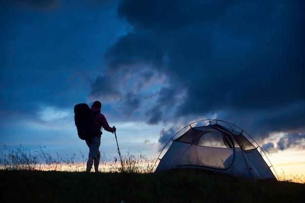 Sparato di un viaggiatore con zaino e sacco a pelo che sta vicino alla tenda sopra una montagna sul tramonto