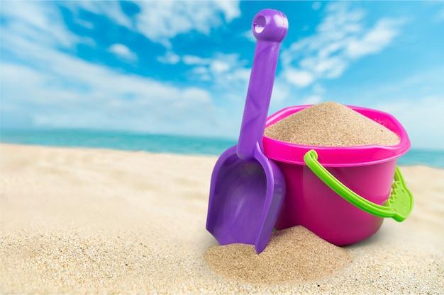 Scatto della spiaggia in una giornata di sole, con una vanga e un secchio