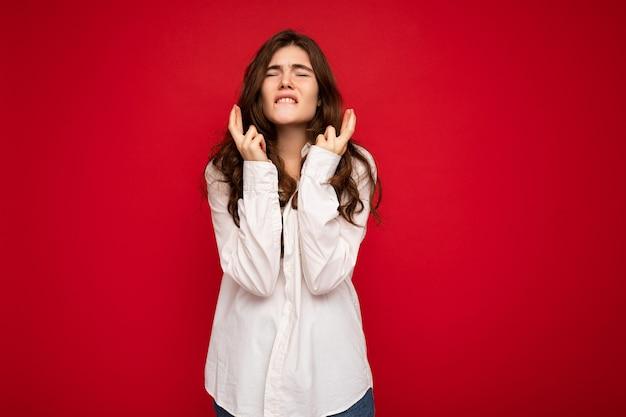 Colpo di bella giovane donna bruna riccia emotiva che indossa una camicia bianca isolata su red