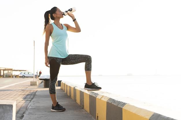 Colpo di bella corridore femminile in piedi all'aperto tenendo la bottiglia d'acqua. donna fitness prendendo una pausa dopo aver eseguito l'allenamento.
