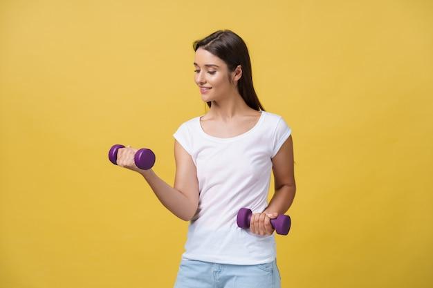 Scatto di una giovane donna bella e sportiva che solleva pesi su sfondo giallo.