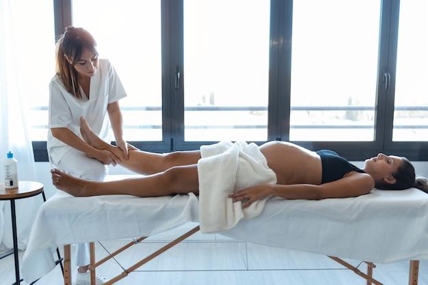 Colpo di bella giovane fisioterapista che massaggia le gambe della donna incinta su una barella a casa.