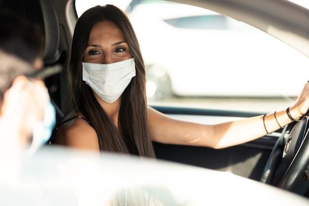 Colpo di bella giovane donna in maschera facciale che guida la sua auto in città mentre guarda e sorride alla sua amica.