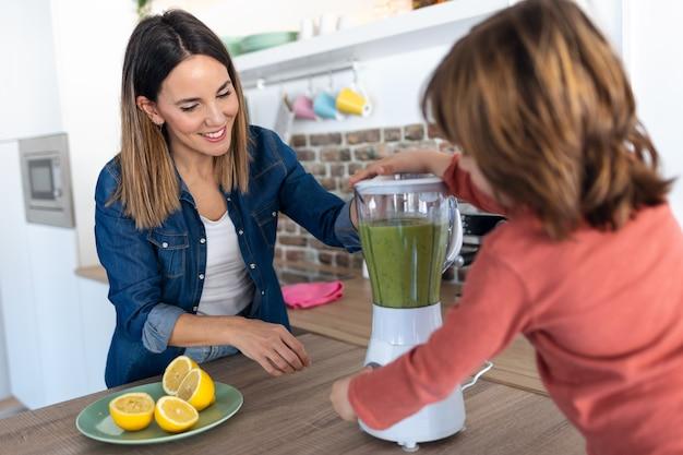Colpo di ragazzo che aiuta sua madre a preparare un succo detox con frullatore in cucina a casa.