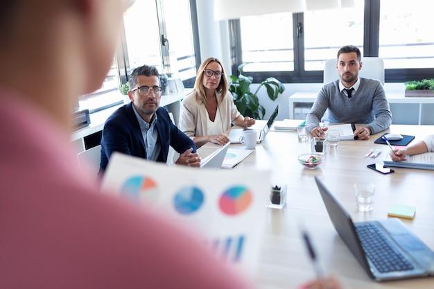Colpo di uomini d'affari che prendono appunti con il laptop e prestano attenzione in conferenza sul luogo di coworking.