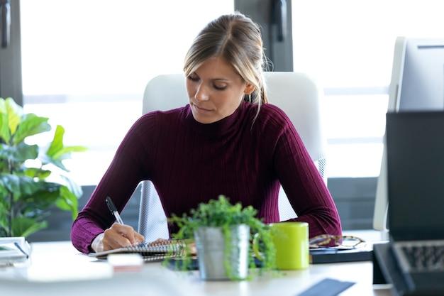 Colpo di giovane donna d'affari concentrata che prende appunti mentre lavora in ufficio.