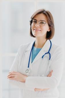 Colpo di fiduciosa dottoressa o chirurgo bruna in piedi con le mani incrociate, indossa un'uniforme bianca, si prende cura della salute dei pazienti pronti a dare consigli in qualsiasi momento. persone, occupazione, concetto di professione