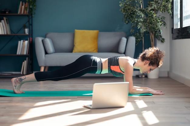 Colpo di fiduciosa giovane donna sportiva che fa esercizi ipopressivi seguendo lezioni di ginnastica online tramite laptop sul pavimento nel suo salotto di casa.