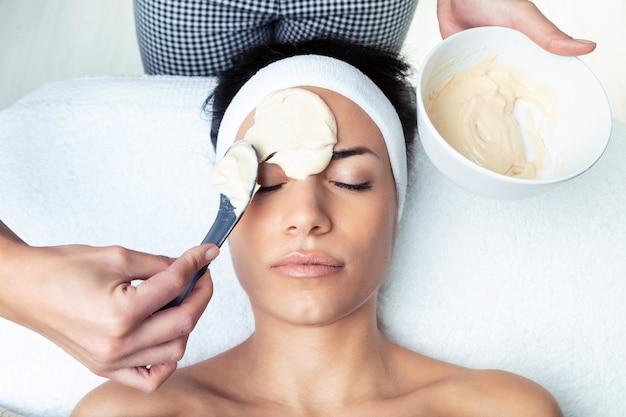 Colpo di cosmetologo che applica la maschera facciale di alginati alla donna nel centro termale.