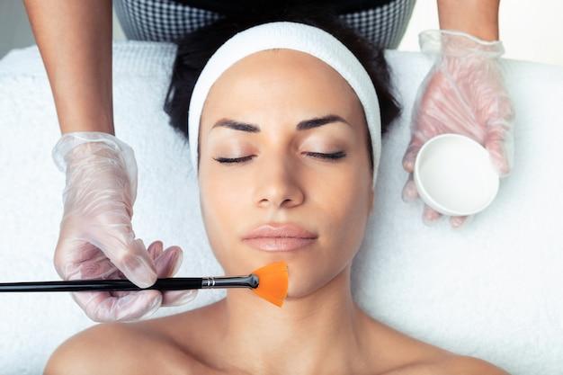 Colpo di cosmetologo che fa un peeling chimico per ringiovanire il viso della donna nel centro termale.