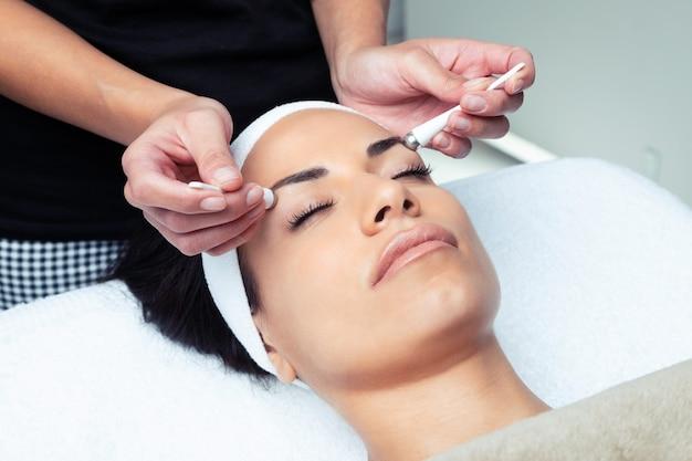 Colpo di cosmetologo che fa la terapia del contorno occhi per il ringiovanimento della donna nel centro termale.