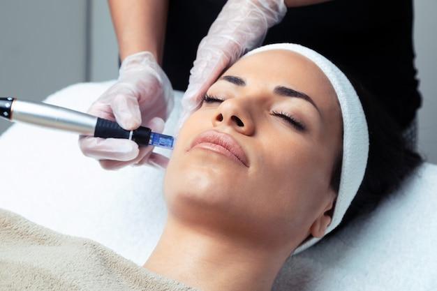 Colpo di cosmetologo che fa l'iniezione di mesoterapia con dermapen sul viso per il ringiovanimento nel centro termale.
