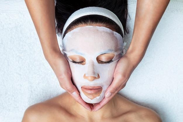 Colpo di cosmetologo che realizza la maschera facciale alla vitamina c per il ringiovanimento della donna nel centro termale.