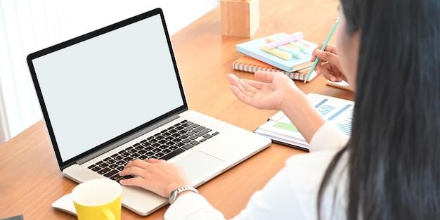 Dietro il colpo della donna creativa che lavora al computer portatile del computer con lo schermo in bianco bianco che mette sullo scrittorio funzionante di legno e circondato dalle apparecchiature per ufficio e stazionario come fondo.