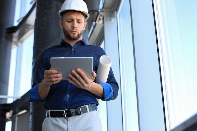 Inquadratura di un ingegnere che utilizza una tavoletta digitale in un cantiere edile. questo software mi aiuta a tenere traccia di tutto.