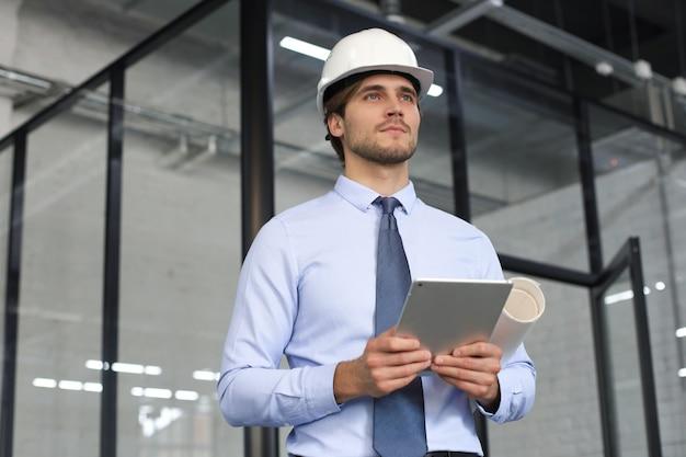 Inquadratura di un ingegnere che utilizza una tavoletta digitale in un cantiere edile.