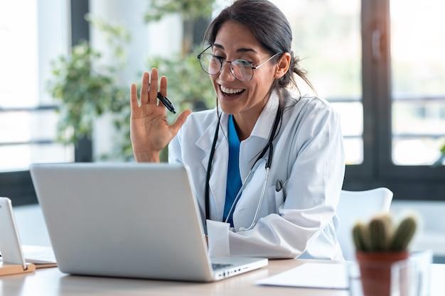Inquadratura di una dottoressa che saluta e parla con i colleghi durante una videochiamata con un laptop durante la consultazione.