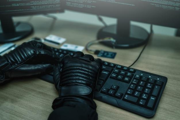 Sparato di spalle all'hacker che irrompe nei server dati aziendali dal suo nascondiglio sotterraneo. vista ravvicinata delle mani degli hacker