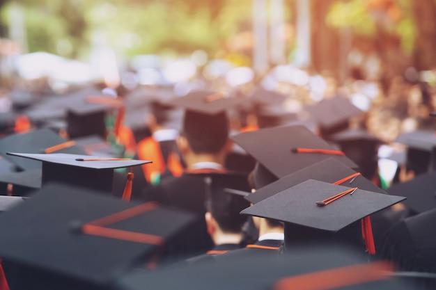 Colpo di cappelli di laurea durante il successo di inizio laureati dell'università, congratulazioni per l'educazione del concetto.