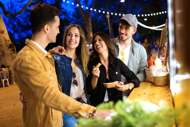 Scatto di un gruppo di giovani amici attraenti che visitano il mercato alimentare e acquistano diversi tipi di fast food nel mercato alimentare in strada.