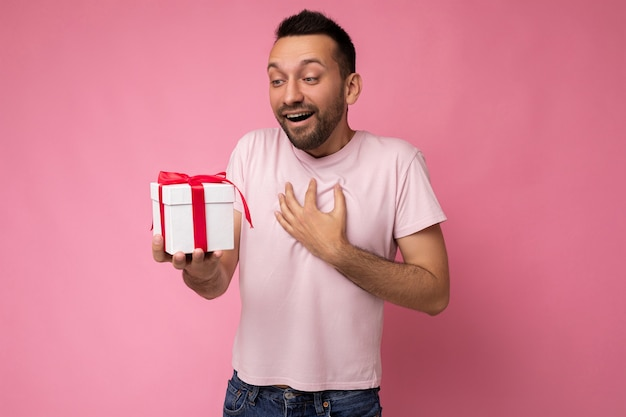 Colpo di bel giovane brunet scioccato felice con la barba isolato su sfondo rosa parete indossando t-shirt rosa che tiene scatola regalo bianca con nastro rosso e guardando il presente
