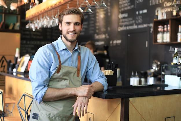 Colpo di felice giovane proprietario del bar in piedi vicino al bancone e guardando la fotocamera, sorridente.