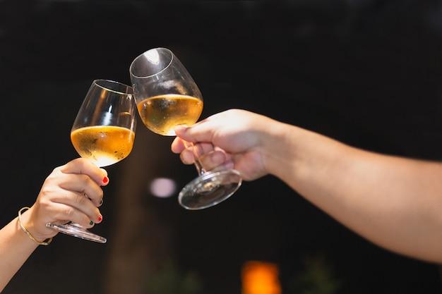 Girato ad alti iso con poca luce coppia che tosta i bicchieri di vino in vacanza.