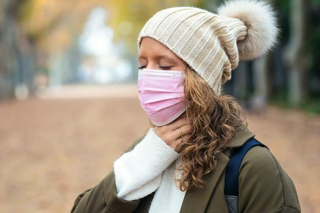 Colpo di malattia giovane donna con terribile mal di gola che cammina per strada.