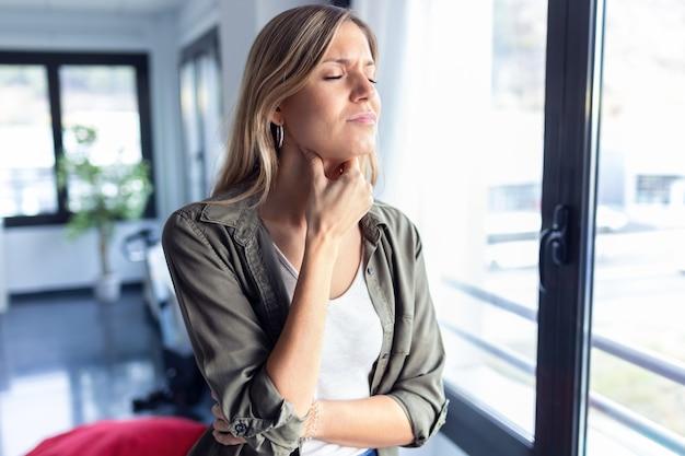 Colpo di malattia giovane donna con terribile mal di gola mentre si trovava nel soggiorno di casa.