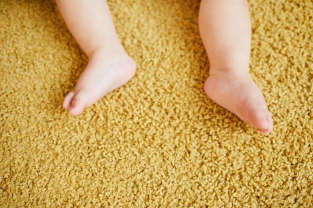 Inquadratura dei piedi del bambino su un tappeto marrone chiaro