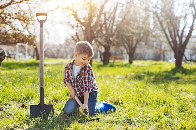 Inquadratura di un bambino seduto su un prato verde primaverile e scavando una buca nel terreno per futuri alberi da frutto in primavera