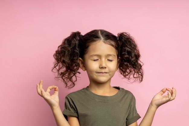 Colpo di piccola ragazza carina calma meditando, chiudendo gli occhi, alzando le mani con gesto zen